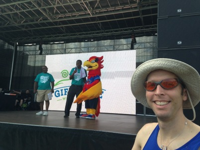 Derek waiting to hear the results of the 10k with Blaze the TGA mascot in back.